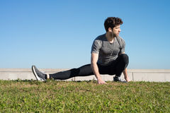 Man stretches leg in the ground Stock Photography