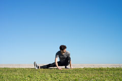 Man stretches the leg in the ground Royalty Free Stock Photography