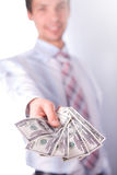 Man stretches money. Man in a white shirt and a red tie on a white background. The businessman holds money in hands. man smiles and stretches money. Dollars are Stock Photos
