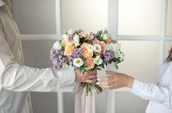 Man stretches out his hands and gives a large bouquet of flowers from roses and lilacs isolated against the background stock images