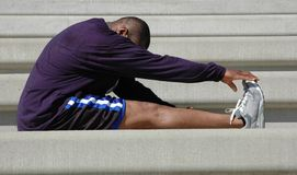 Man Stretches for Race. Man warms up and stretches before and after race Royalty Free Stock Images