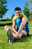 Man Stretching. Handsome runner stretching and smiling in park Royalty Free Stock Photo