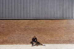 Man Stretching Against Brick Wall Stock Image
