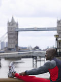 Man Stretching Against Tower Bridge In England Royalty Free Stock Image