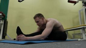 Man stretching arm before gym workout. Fitness strong male athlete standing indoor warming up. Sporty man stretching arm before gym workout. Fitness strong male stock footage
