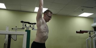 Man stretching arm before gym workout. Fitness strong male athlete standing indoor warming up. Sporty man stretching arm before gym workout. Fitness strong male stock video footage