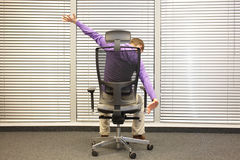 Man stretching arms sitting on chair in office. Back view royalty free stock images