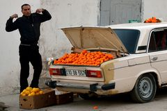 Man stretching in Baku, capital of Azerbaijan, next to car showing oranges for sale in the boot royalty free stock photo