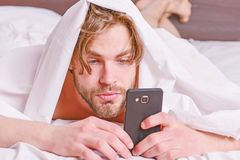 Man stretching in bed. Lazy man happy waking up in the bed rising hands in the morning with fresh feeling relaxed. Man royalty free stock photo