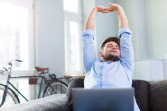 Man stretching on couch. Young man relaxing at home Royalty Free Stock Photo