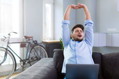 Man stretching on couch. Young man relaxing at home Royalty Free Stock Photos