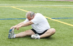 Man stretching exercising field