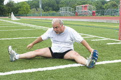 Man stretching exercising sports field Stock Images