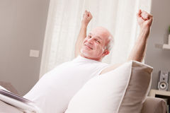 Man stretching and going asleep. In his living room but he could also exult, who knows Stock Images