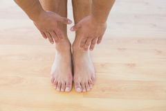Man stretching hands towards his feet on parquet floor Stock Photo