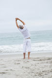 Man stretching his arms by the sea Royalty Free Stock Photos