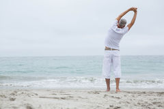 Man stretching his arms by the sea Stock Photography