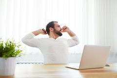 Man stretching his back at desk Royalty Free Stock Photo