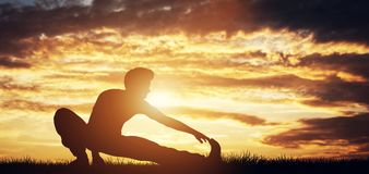 Man stretching his body in the sunset Royalty Free Stock Photos