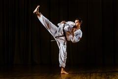 Man stretching his leg while kicking. Karate motion royalty free stock image