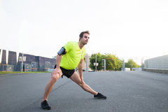 Man stretching his legs in urban setting while standing on the road Royalty Free Stock Image