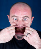 Man stretching his mouth to make a funny face. Studio shot Royalty Free Stock Photography