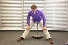 Man stretching in his office Royalty Free Stock Images