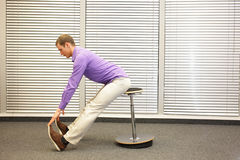 Man stretching in his office - profile Stock Images