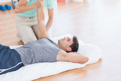 Man stretching with his trainer Royalty Free Stock Photo