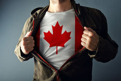 Man stretching jacket to reveal shirt with Canada flag Stock Image