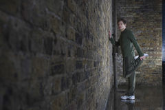 Man Stretching Leg Against Brick wall Stock Images