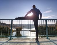 Man is stretching legs in break from run. Sun is outlining man body. stock photo