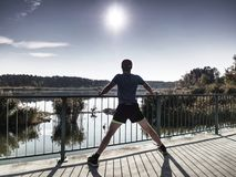 Man is stretching legs in break from run. Sun is outlining man body. stock image