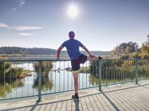 Man stretching legs before run outside within sunny morning. royalty free stock photography