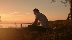 Man stretching legs before yoga practice. Young flexible man sitting on the beach and doing stretching exercises before yoga practice. Summer time, sunset stock video