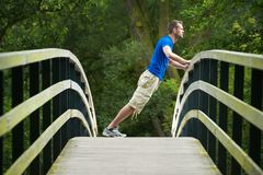 Man Stretching Muslces Outdoors. Portrait of a young man doing stretching exercises outdoors royalty free stock images