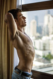 Man stretching near window. Young shirtless man stretching with eyes closed near window. Vertical indoors shot Stock Image