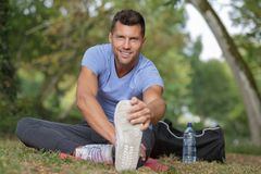Man stretching before running on forest trail. Man stretching before running on a forest trail Royalty Free Stock Image