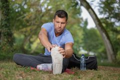 Man stretching before running on forest trail. Man stretching before running on a forest trail Stock Photography
