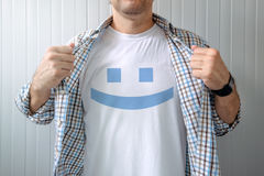 Man stretching shirt to reveal smiley emoticon Stock Photography
