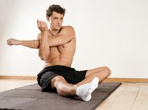 Man stretching shoulder muscles. Photo of a young attractuive man stretching his shoulder muscles while sitting on exercise mat stock photography