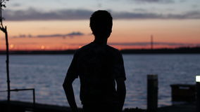 Man stretching at sunset near the river stock footage
