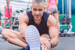 Man stretching and woman doing dumbbells exercises Stock Photos