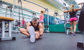 Man stretching and women doing dumbbells exercises Royalty Free Stock Image