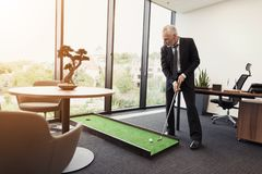 A man in a strict business suit plays in an office in a mini-golf. A man in a business suit plays mini golf. He is in a modern modern office Stock Images