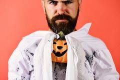 Man with strict face expression on red background. Guy with beard holds orange pumpkin with smile. Halloween and happy holiday concept. Halloween character in royalty free stock photos