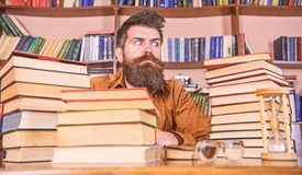 Man on strict face sit between piles of books, while studying in library, bookshelves on background. Bookworm concept. Teacher or student with beard sit at royalty free stock image