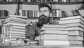 Man on strict face sit between piles of books, while studying in library, bookshelves on background. Bookworm concept. Teacher or student with beard sit at stock photo