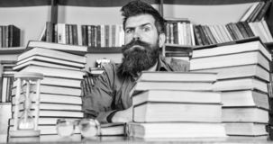 Man on strict face sit between piles of books, while studying in library, bookshelves on background. Teacher or student. With beard sit at table with hourglass stock photos