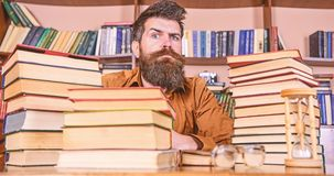 Man on strict face sit between piles of books, while studying in library, bookshelves on background. Teacher or student. With beard sit at table with hourglass stock image